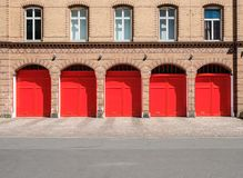 Fire department builidng facade with red doors and empty street.  royalty free stock images