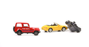 Fire department at car crash. Car crash between a yellow sportscar and a black sedan with fire dept car. Simulation with model cars royalty free stock images
