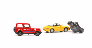 Fire department at car crash. Car crash between a yellow sportscar and a black sedan with fire dept car. Simulation with model cars stock image