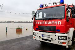 Fire department car on the flooded shore of a river.  stock photography