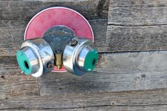 Fire Department Connection. Twin fire hose fitting splitter, also know as Siamese connection sticking out of wooden wall royalty free stock photography