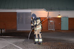 Fire department putting out arson. Swedish fire department putting out fire right next to a school in poorest parts of Malmo city. Arson is now a daily Royalty Free Stock Photography