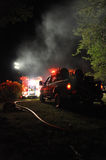 Fire Department On Scene. A fire department is deployed for a forest fire at night, scene illuminated by overhead work lights and vehicle lights royalty free stock image
