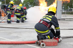Fire department training. Firefighters spraying water in fire fighting training operation royalty free stock image