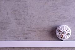 Fire detector installed on a concrete wall. Fire detector installed on a concrete gray wall Royalty Free Stock Photo