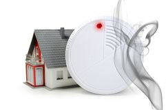 Fire detector with red alert while smoke rises. Fire and smoke detector with red alert while smoke rises royalty free stock photo