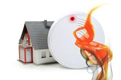 Fire detector with red alert while smoke rises royalty free stock photography