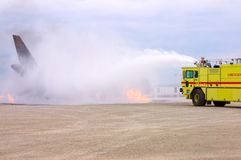 Fire Drill. A yellow fire truck spreading white foam on what appears to be a burning plane Stock Photography