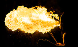 Fire eater from behind. On black background Royalty Free Stock Image