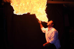 Fire-eater flame. Fire-eater with flame over dark background Royalty Free Stock Photos