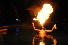Fire Eater. Muscular fire-eater in a pool at night blows a golden flame from his mouth. Exciting fire-eating act was entertaining guests at a hotel in Mauritius Stock Photo