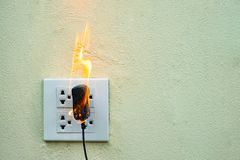 On fire electric wire plug Receptacle and adapter on white background. Electric short circuit failure resulting in electricity wire burnt royalty free stock images