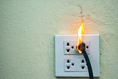 On fire electric wire plug Receptacle and adapter on white background. Electric short circuit failure resulting in electricity wire burnt royalty free stock photo