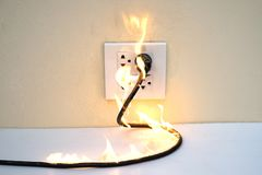 On fire electric wire plug Receptacle wall partition. Electric short circuit failure resulting in electricity wire burnt royalty free stock photo