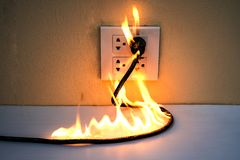 On fire electric wire plug Receptacle wall partition. Electric short circuit failure resulting in electricity wire burnt royalty free stock photography