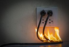 On fire electric wire plug Receptacle wall partition. Electric short circuit failure resulting in electricity wire burnt stock photos