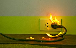 On fire electric wire plug Receptacle wall partition. Electric short circuit failure resulting in electricity wire burnt stock photo