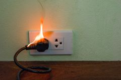On fire electric wire plug Receptacle wall partition. Electric short circuit failure resulting in electricity wire burnt stock image