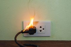 On fire electric wire plug Receptacle wall partition. Electric short circuit failure resulting in electricity wire burnt royalty free stock photos