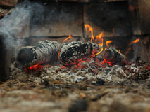 Fire. Embers and fire above firebrand in hearth, shallow DOF Royalty Free Stock Photography