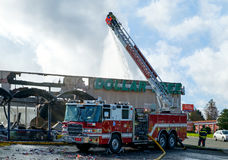 Fire engine at fire scene. Kent, WA, USA November 14, 2016: Fireman operates water nozzle on extension boom of fire engine at scene of fire at Dollar Tree store Stock Images