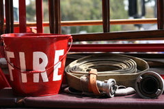 Fire engine pail and hose. Fire engine pail in red with the words FIRE on it and a fire hose Stock Photography