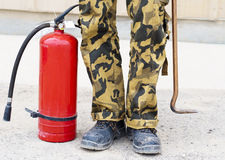 Fire equipment. The fire extinguisher stands near feet of the firefighter Royalty Free Stock Photo