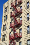 Fire Escape. Red fire escape on the light color building with the shadows stock photo