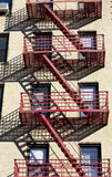 Fire Escape. Red fire escape on the light color building with the shadows stock photography
