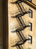 Fire-escape. External metallic staircase on the wall of the yellow house Royalty Free Stock Photography