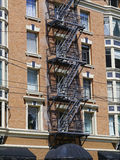 Fire escape creates interesting pattern on a building. The outlines of the metal framework of a fire escape serves as an interesting foreground to the facade of stock photo