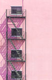 Fire escape metal on  light pink Vintage stone wall outside buil Royalty Free Stock Image