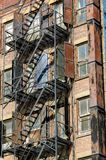 Fire escape in Soho, Manhattan, New York. Fire escape on an old brick wall building with its rusted metal shutters, Soho, Manhattan, New York City Stock Image