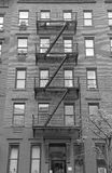 Fire escape stairway on exterior of red brick walkup apartment building Stock Photos