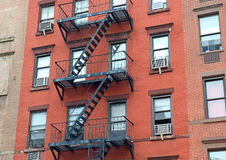 Fire escape stairway on exterior of red brick walkup apartment building Stock Photo