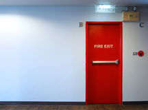 Fire exit emergency door red color metal material. Fire exit emergency door red color metal material with alarm for safety protection and wood floor and white Stock Image
