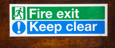 Fire exit Keep clear. Warning sign for Fire exit keep clear attached to a wooden door Royalty Free Stock Photos