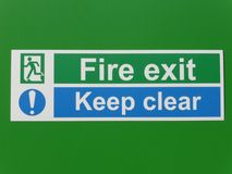 Fire Exit and Keep Clear Sign on a Green Background Royalty Free Stock Images