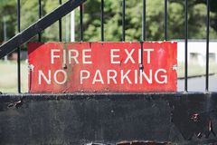Fire exit no parking sign entrance gate guarded secure workplace station brigade red black. Uk royalty free stock images