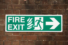 Fire exit sign. On a grunge wall background Royalty Free Stock Photo