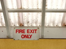 Fire Exit Sign. Fire Exist sign near ceiling of outdoor cafe with transparent roofing Stock Image