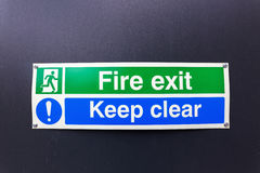Fire exit sign on black wall. Fire exit sign on a black wall Stock Images