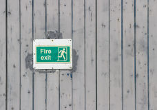 Fire exit sign. Faded fire exit sign on an outside door Royalty Free Stock Photo