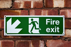 Fire exit sign on the red clay brick wall.  Royalty Free Stock Photo