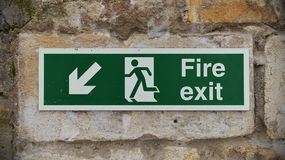 Fire Exit Sign. View of a Generic Fire Exit Sign on a Stone Wall Royalty Free Stock Image