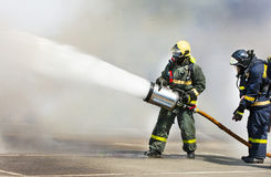 Fire extinguish the fire with foam in the smoke. Royalty Free Stock Photos