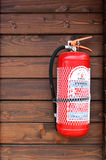 Fire extinguisher. Hanged on a wooden house cabin royalty free stock photos