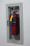 Fire extinguisher behind glass. A red fire extinguisher behind a glass door on a wall Stock Images