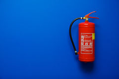 Fire Extinguisher on Blue. Fire extinguisher on the blue wall Royalty Free Stock Photo