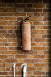 Fire Extinguisher on brick wall Royalty Free Stock Photography